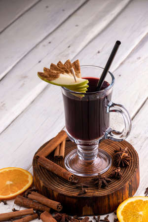 Glass of mulled wine. Spicy warming Autumn and winter drink on light background