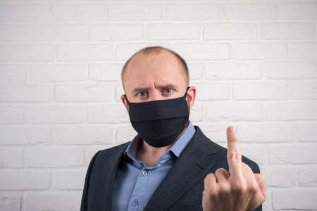 angry man in a mask shows the fuck Stock Photo