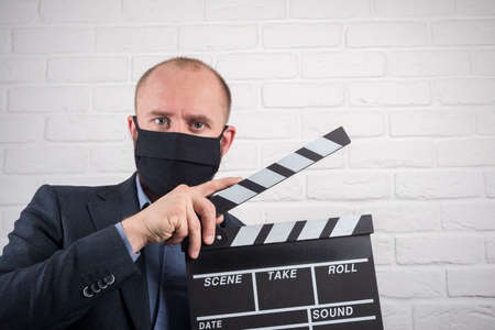 Man in jacket in virus mask with clapperboard on white background Stock Photo