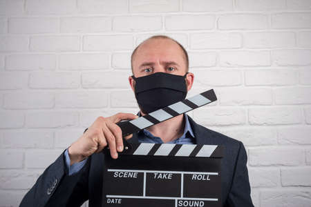 Man in medical mask with clapperboard