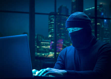 Malware concept. Hacker uses laptop
