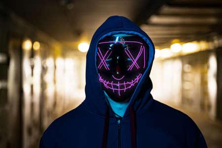 neon masked criminal on the dark. Selective focus Stock Photo