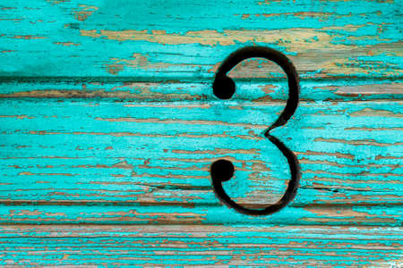 The number 3 on the green rustic boards Standard-Bild