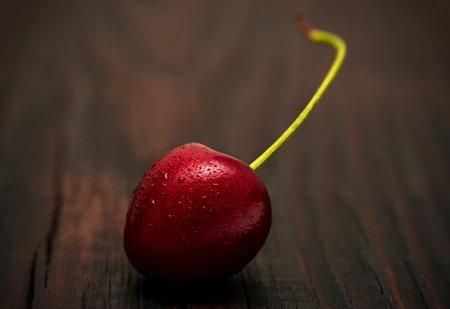 Cherries in low key lighting on dark wood background