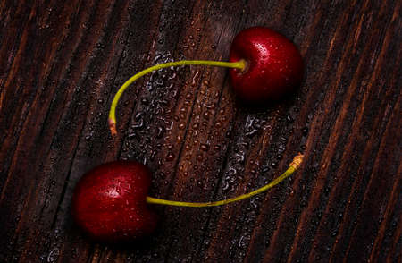 Cherries berries in low-key lighting on dark wood background