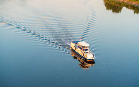 Evening. A small passenger ship sails on the river