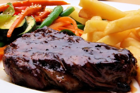 Grilled juicy steak with vegetables and chips Stock Photo