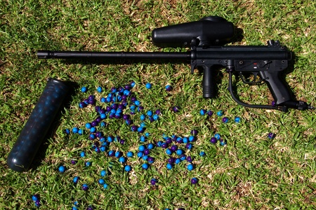 Paintball marker and pod with paintballs on the grass