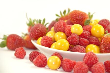 Raspberries, gooseberries and strawberries on the white plate Stock Photo