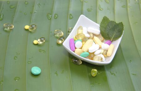Assorted pills on leaf background photo