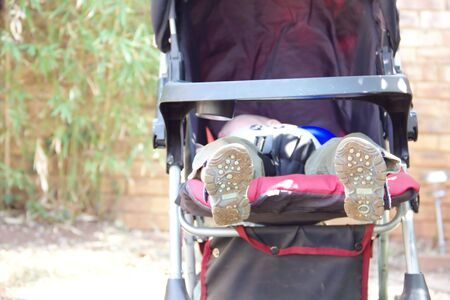 Feet of tired little boy sleeping in a stroller photo