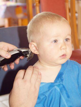 Little boy getting his first haircut photo