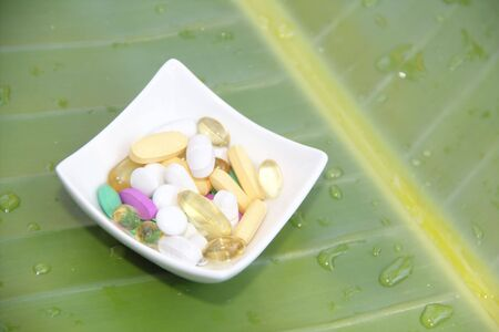 Mixed vitamins on the white plate on leaf background Stock Photo