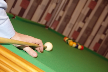 Man hand with a cue is plaing billiard