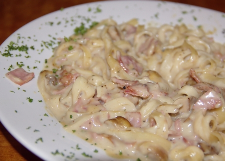 Juicy tasty pasta Alfredo on white plate