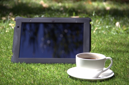 Tablet pc and a cup of coffee on the grass Stock Photo - 15427383
