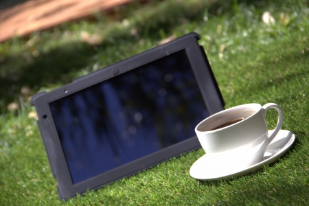 Black tablet pc and a cup of coffee outdoors Stock Photo - 15427541