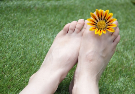 Woman feet on the grass with flower