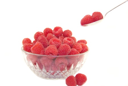 Delicious raspberries in a plate with a spoon on white