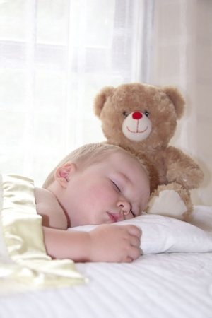 One year old boy is sleeping with teddy bear photo