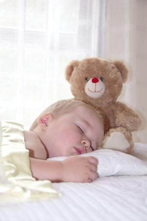 One year old boy is sleeping with teddy bear