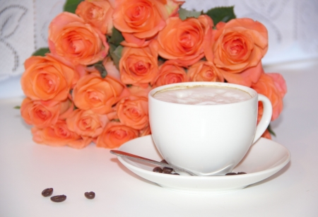 Rose flowers and a cup of coffee with foam