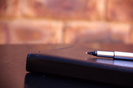 Luxury pen and notebook on a black table Stock Photo - 18618978