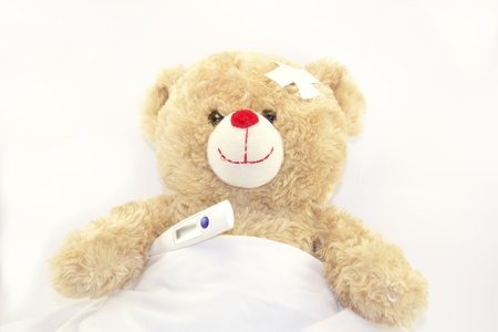 Teddy bear with a thermometer isolated on white background