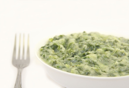 creamed: Creamed spinach in a white plate with fork on white background