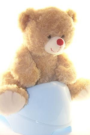 Cute teddy bear is sitting on the potty Stock Photo