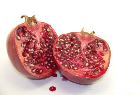 Halves of pomegranate fruit isolated on white background Stock Photo