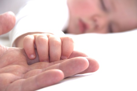Sleeping toddler boy is holding fathers hand Stock Photo