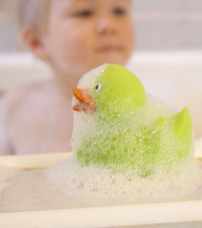 Bath duck and toddler boy behind