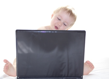 Little boy is  having fun with a computer on white background Stock Photo