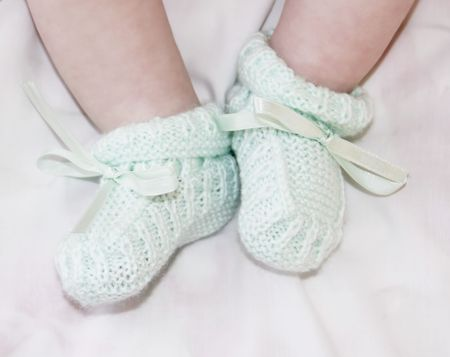 Tiny baby feet in light green baby bootees photo