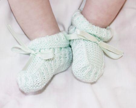 Tiny baby feet in light green baby bootees Stock Photo