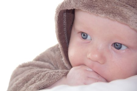 Face of cute baby with hand in mouth and white space