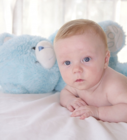 Cute three months old baby and blue teddy bear