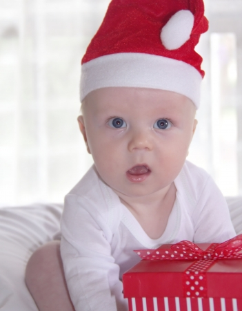 Cute baby in red new year hat with present