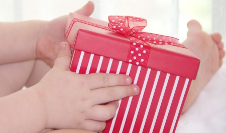 Little child is holding and opening the red gift box