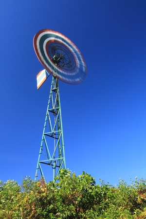 Water pumping windmills for pumping water with spinning blades against a blue sky with clouds. Stock Photo