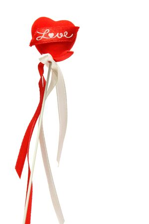 A isolated red heart-shaped wand with white ribbon on white background