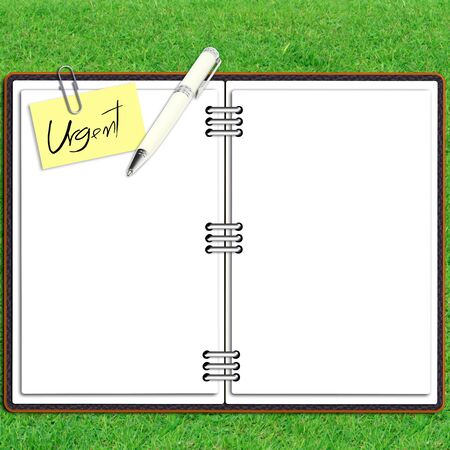 Paper note book leather cover with pen and sticky paper urgent text over grass photo
