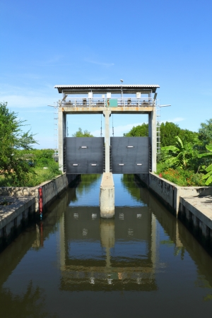 sluice: A sluice is a water channel controlled at its head by a gate. A sluice gate is traditionally a wood or metal barrier sliding in grooves that are set in the sides of the waterway.