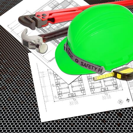 Green Helmet of Safety Officer constructor with blueprints building construction and tools, metal tape measure, hammer, wrench