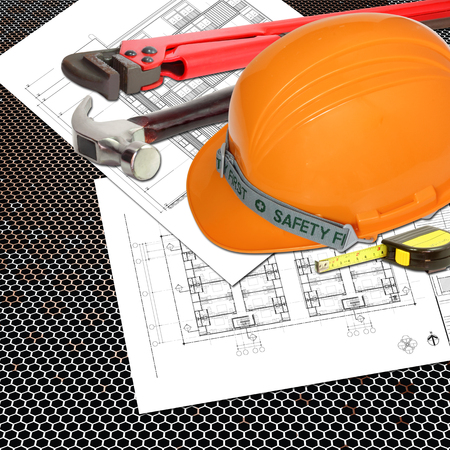 Orange Helmet of relate or rescue constructor with blueprints building construction and tools, metal tape measure, hammer, wrench