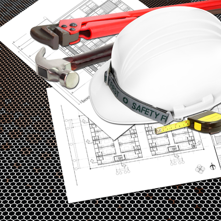 White Helmet of inspectors or engineer constructor with blueprints building construction and tools, metal tape measure, hammer, wrench