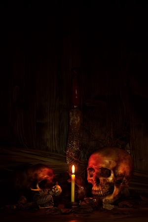 Still life scene have two skulls; one skeleton; candle; knife. The scene show skull atmosphere under candlelight for halloween night festival
