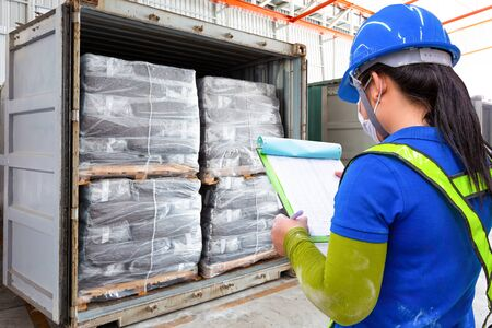 Staff is checking the list items of product in containers in the warehouse that meets the customer's order before delivery to the destination address.