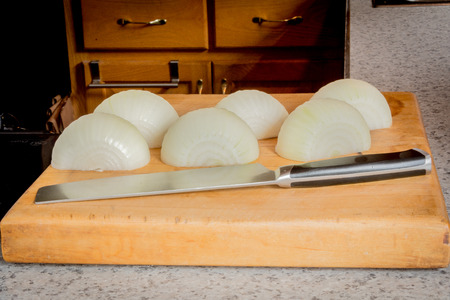 A knife and peeled onions on a butcher block cutting board.